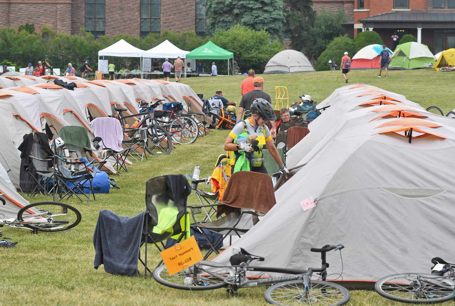 TENT CITY — In the foreground, cyclists unpack their supplies and settle in for a night on the Fort Stanwix lawn. At the check-in tents at back, near St. Peter's, cyclists could learn information on area restaurants and entertainment options. A shuttle bus service was also available for the tourists.