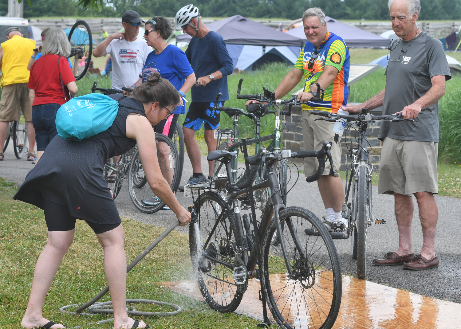 "WASHING OFF THE DIRT — Leslyn Hall from Burlington, Vermont hoses off her bike at Fort Stanwix Thursday afternoon. She said this was her first tour and that it was an ""awesome"" experience. ""So amazing how communities turn out as we are going through them,"" Hall added."