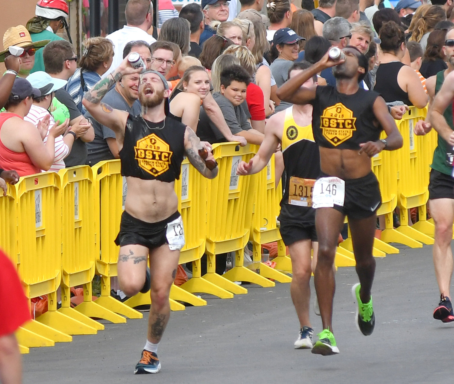 CHEERS — Garden State Track Club teammates Brendan Conway of Ridgefield Park, NJ, left, and Sean Donohue, Keyport, NJ, each chug a Utica Club beer on their way to the finish line at the Boilermaker 15K. Both finished the race in 1:04:26.