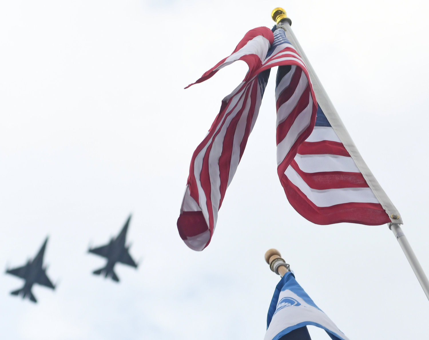 SPEED ON DISPLAY — Two F-16 fighter jets perform a flyover at the 42nd annual Boilermaker road race in Utica Sunday toward the end of the 15K. The flags sit atop the finish line outside the F.X. Matt Brewing Co.