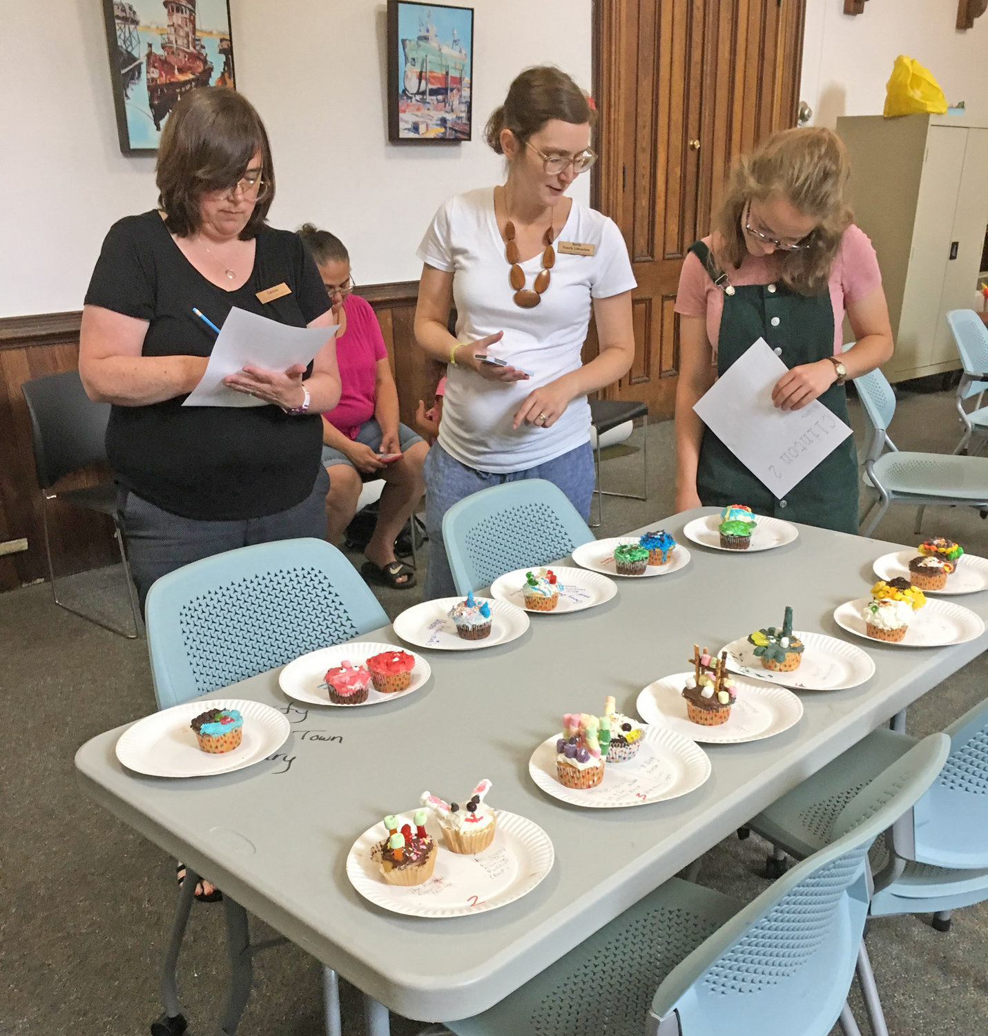 TOUGH DECISION — Kirkland Town Library Assistant Director Laura Stoll, Youth Librarian Ruth Gilbert and Avery Cook look over and judge the cupcake designs to be awarded prizes during the library's Teen Cupcake Wars.