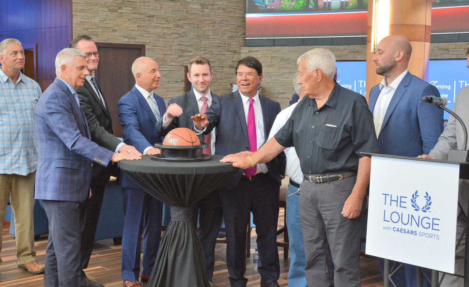 "EYES ON THE BALL— Oneida Nation CEO Ray Halbritter leads the pack in pushing the basketball start device launching the new ""The Lounge with Caesars Sports"" sports book on Thursday, Aug. 1 at the Turning Stone Casino. Pictured from left are Super Bowl LIV prize winner Peter Cantalupe; Oneida County Executive Anthony J. Picente Jr.; Verona Town Supervisor Scott Musacchio; the head of Scientific Games Howard Glaser; Senior Vice President of Strategic Development at Caesars Entertainment Walt Fales; Halbritter; Wolf Clan member Chuck Fougnier and President of the Utica Comets Rob Esche."