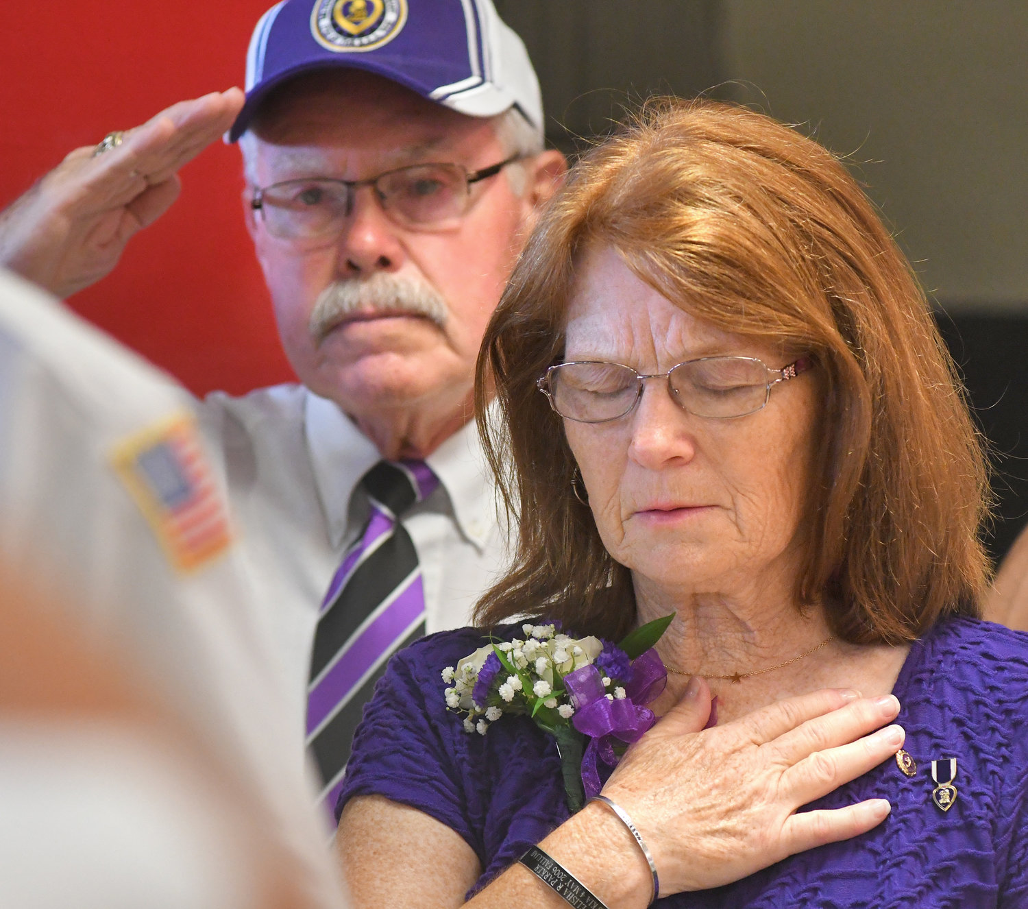 HONORING AND REMEMBERING — Gold Star mother Donna Parker and her husband Renny Parker stand during the playing of Taps at a National Purple Heart Day wreath-laying ceremony Wednesday at the Utica Memorial Auditorium. Their son, Marine Corps Sgt. Elisha R. Parker of Camden, was killed in action in Iraq on May 4, 2006, at age 21. The ceremony Wednesday was by CNY Chapter 490 Military Order of the Purple Heart of the USA. Additional photos online at www.romesentinel.com.