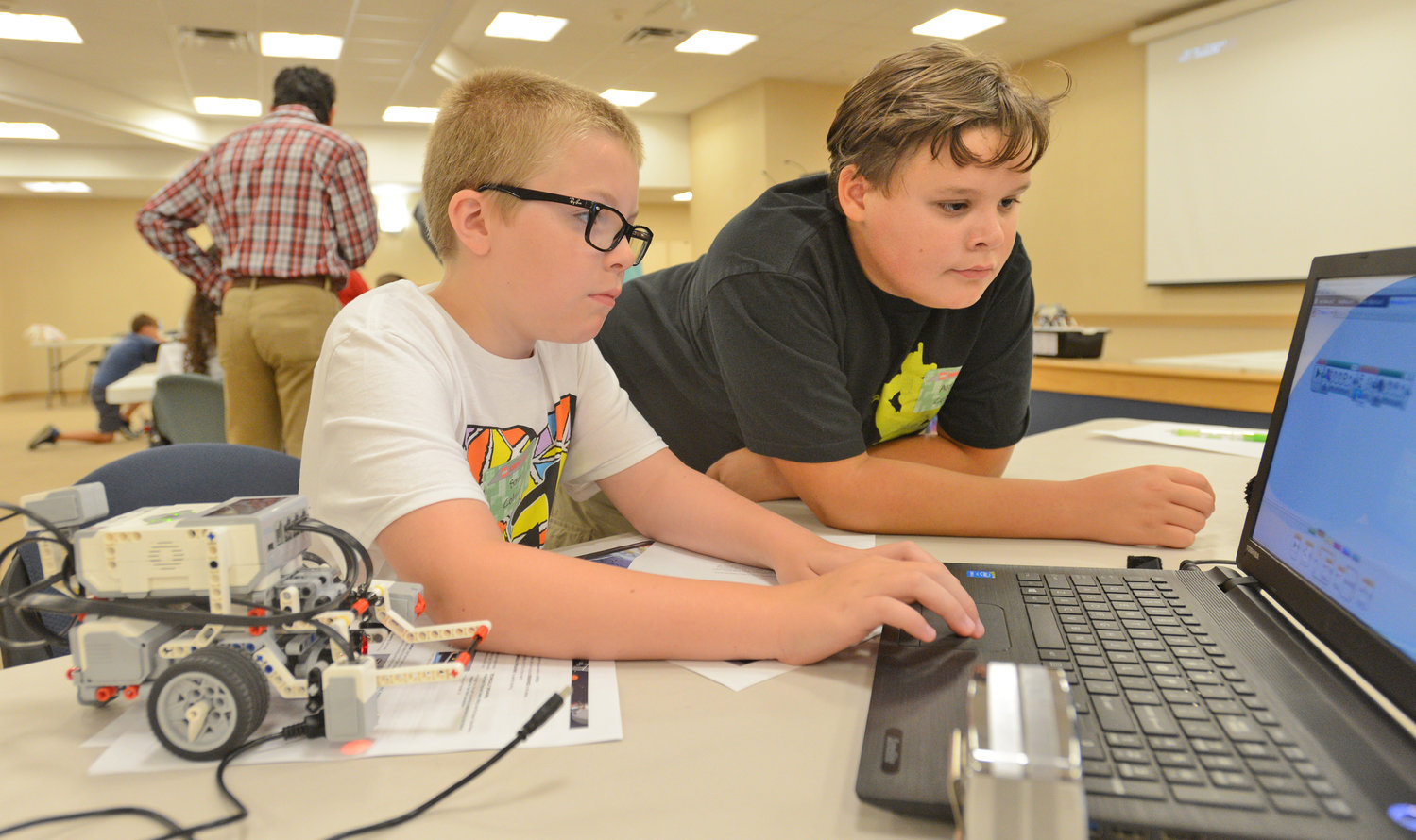 CHECKING THE PROGRAMMING — Denti Elementary School students Sam Colmey and Aidan Curry are at the keyboard to program their Lego robot for tasks to perform, during a STEM (science, technology, engineering, math) Outreach Program camp Wednesday at Griffiss Institute. The week-long Lego robotics camp, in conjunction with Rome Lab which is formally called the Air Force Research Laboratory Information Directorate, includes students in grades 5-8 who are learning how to build and program robots.