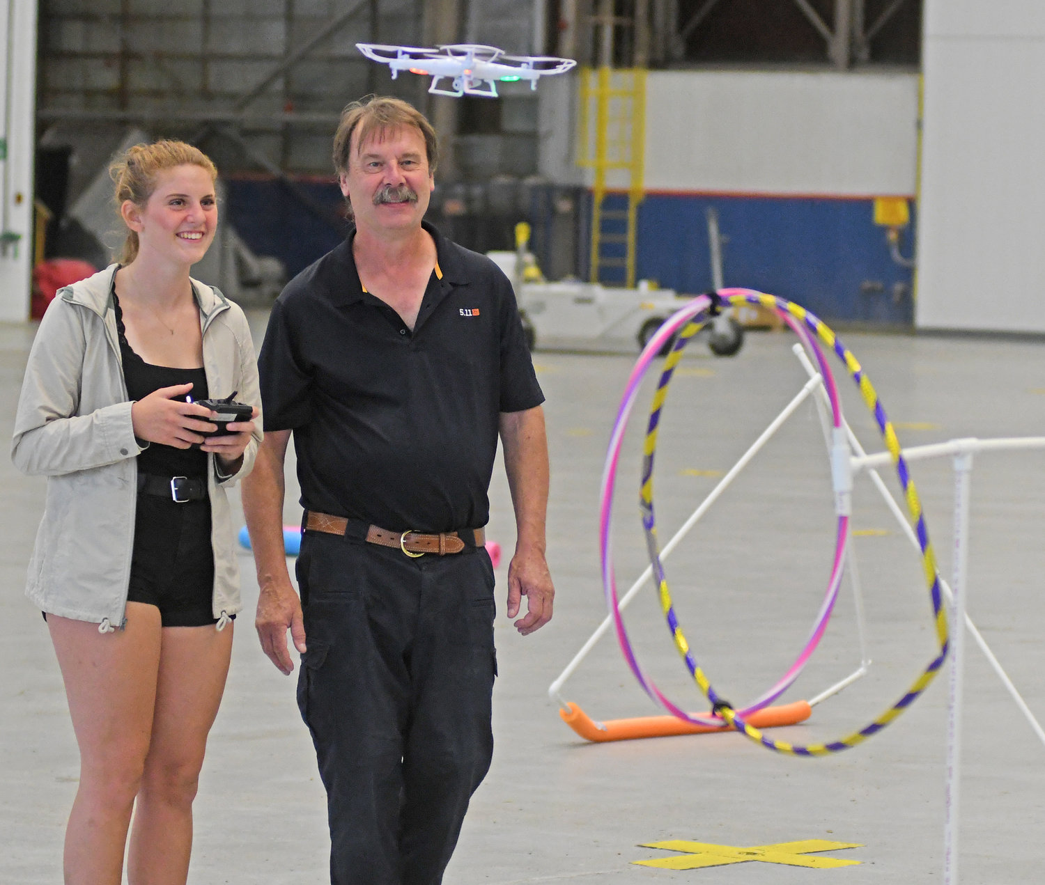 ON THE MOVE — Paige Novak, of Vernon-Verona-Sherrill High School, flies her drone through an obstacle course in Building 100 at Griffiss Business Park as instructor Bill Judycki looks on.