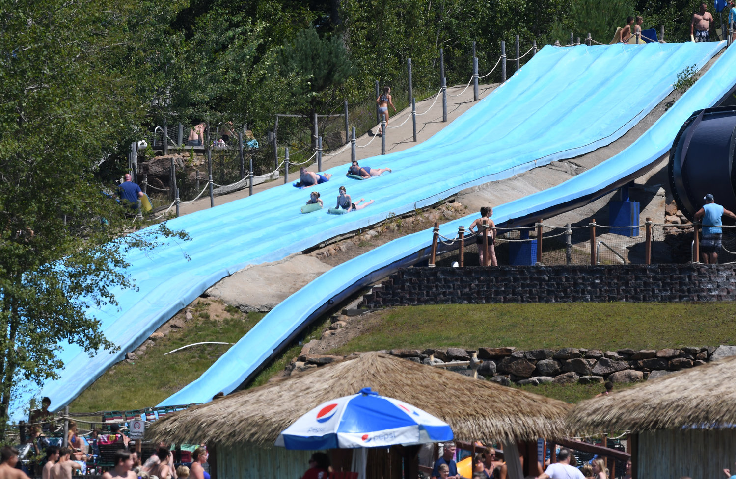 SLIP SLIDING AWAY — Riders on mats zip down the Serengeti Surf Hill, on the left, at the Enchanted Forest Water Safari theme park earlier this week. The popular park, which boasts more than 200,000 visitors each summer, has announced plans to replace the popular mat ride, along with another older slide, Killermanjaro, shown on the right. The work will be performed after the park closes for the season in September with the new rides being up and ready for action at the start of next season in June 2020.