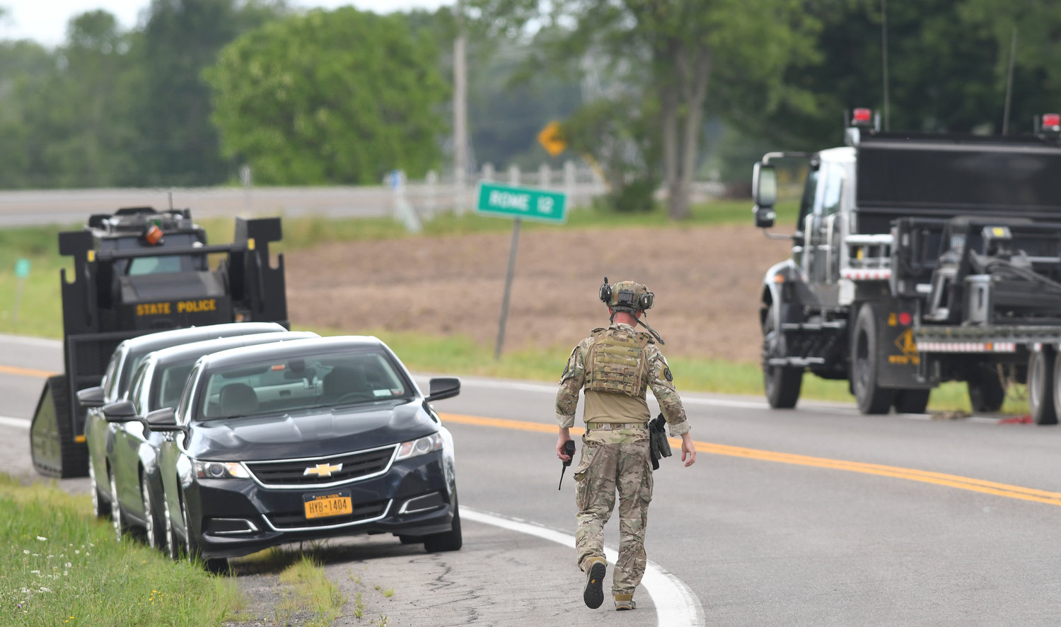 READY AND WAITING — A SWAT trooper waits in the law enforcement staging area at routes 31 and 46 during Friday afternoon's standoff. State police said the suspect surrendered peacefully after about five hours.