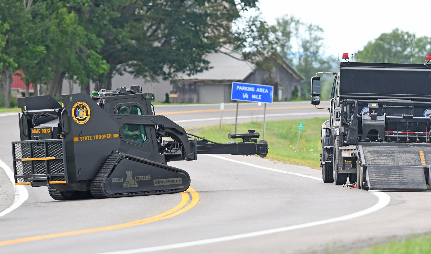 BATTERING RAM READY — A New York State Police Bobcat with battering ram attachment stages near the stand-off on Route 46 in Verona Friday afternoon. State police said an armed man was barricaded inside a barn. Troopers said the man agreed to surrender peacefully, and the battering ram was not used.