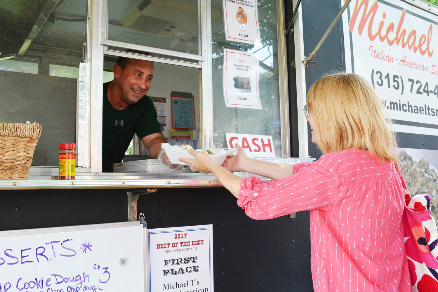 GREENS TO GO — Michael Trunfio, owner of Michael T's food truck hands customer Nicolle Child an order at the Farmer's Market on the Clinton Green, Thursday, Aug. 8. The Clinton resident has been operating the food truck in the village market for the past three years, but said this is his busiest year to date.