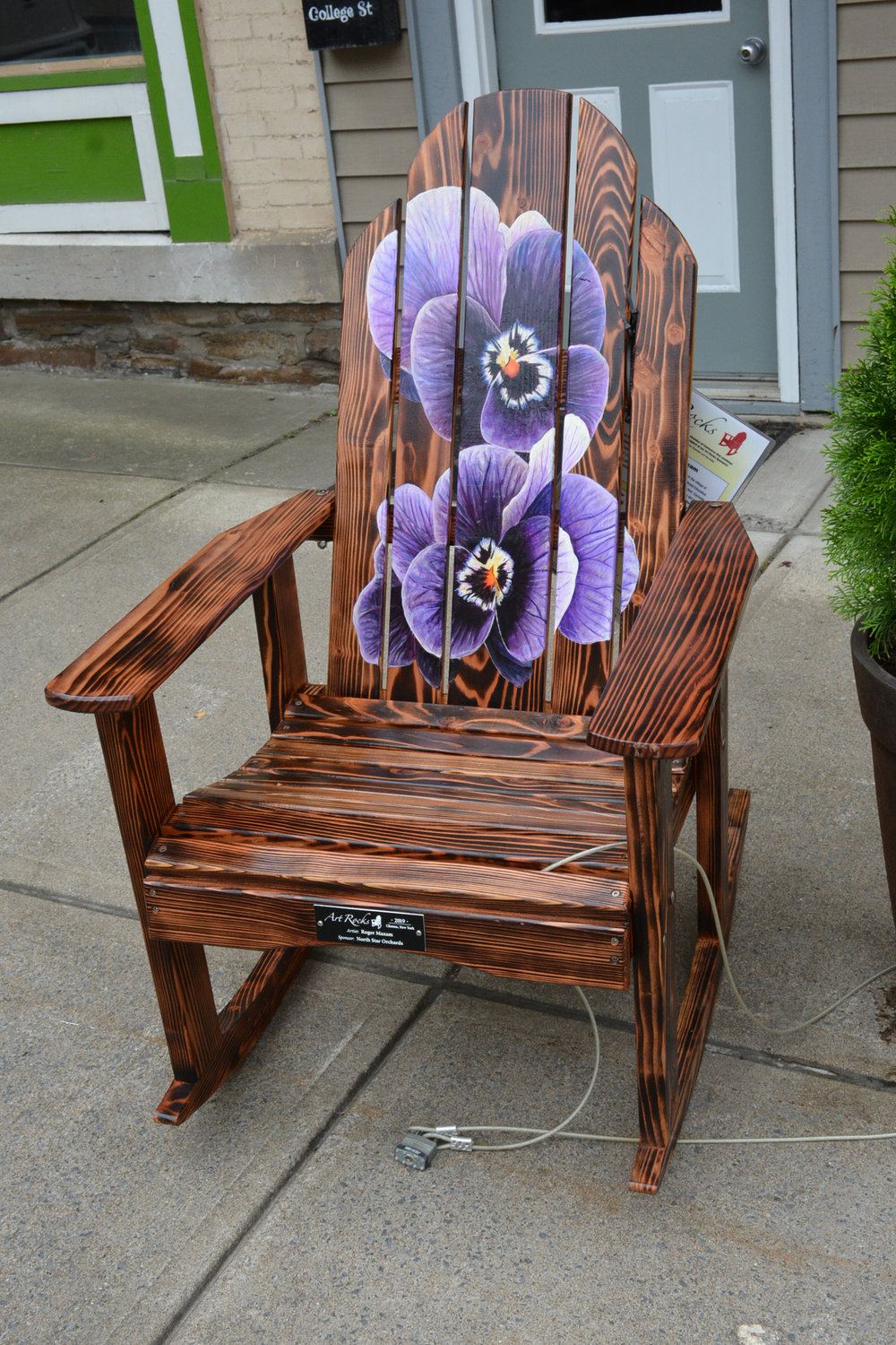 ROCKING, ROCKING CHAIR—ART ROCKS! — This is one of the many chairs and benches painted by local artists that will be auctioned off at 4:30 p.m. Saturday, Aug. 24 during the annual Clinton Art & Music Festival. This chair was painted by Roger Maxam.