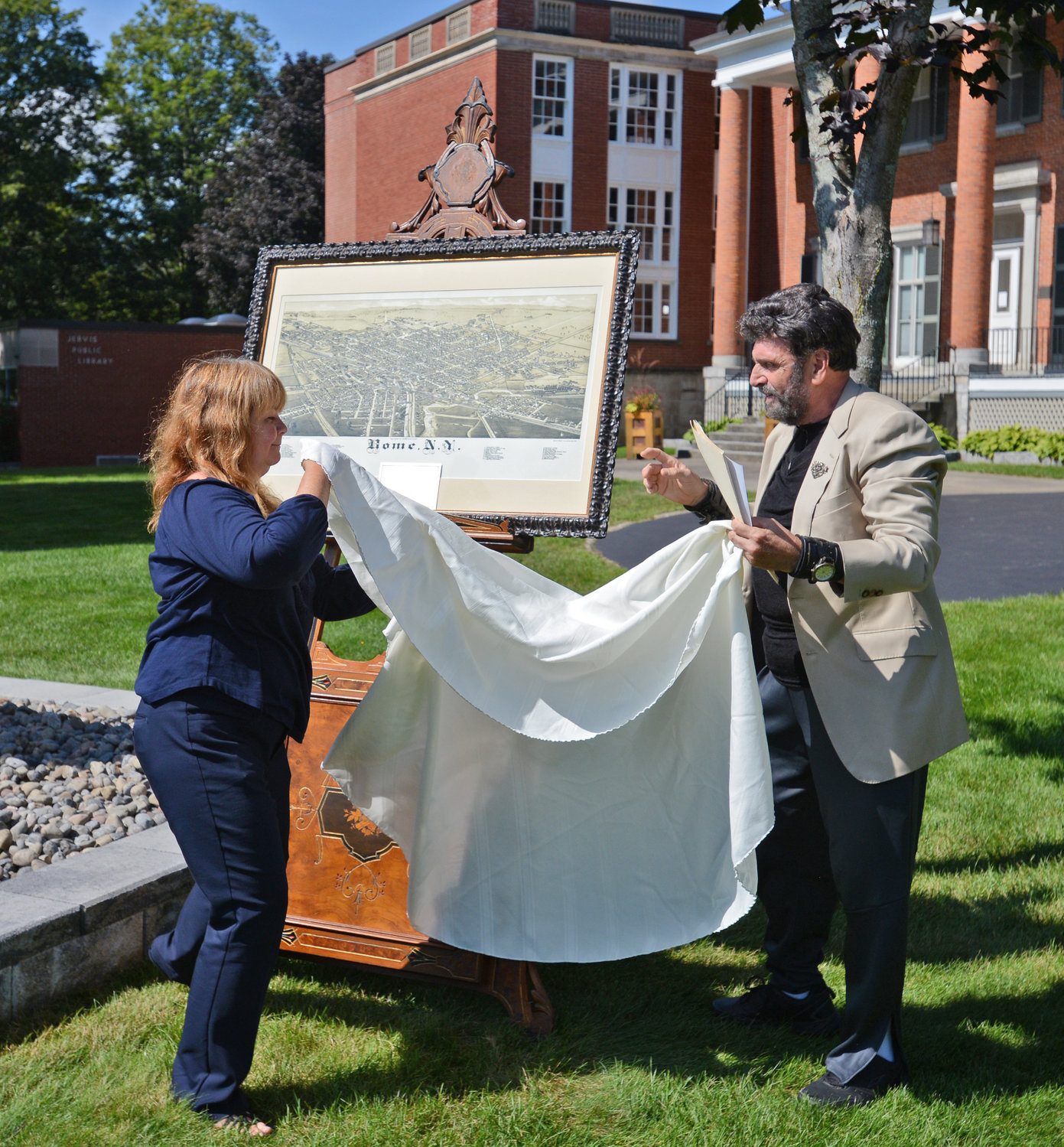 UNVEILING — Lori Chen and Steven Strange unveil the 1886 Lithograph map of Rome that was donated to Jervis Library and will be displayed in the Dillon Room.