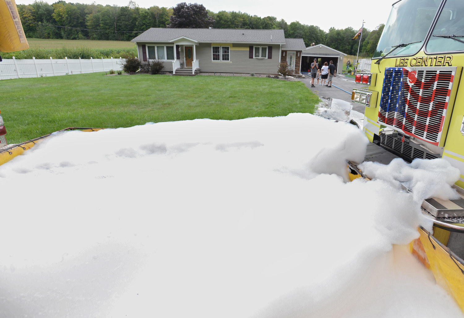 FOAM FIGHT — A pool of firefighting foam was built up by the Lee Center Fire Department to help battle a garage fire on Kiwanis Road Thursday afternoon. Fire officials said no one was injured and the residence was spared. (Sentinel photo by John Clifford)