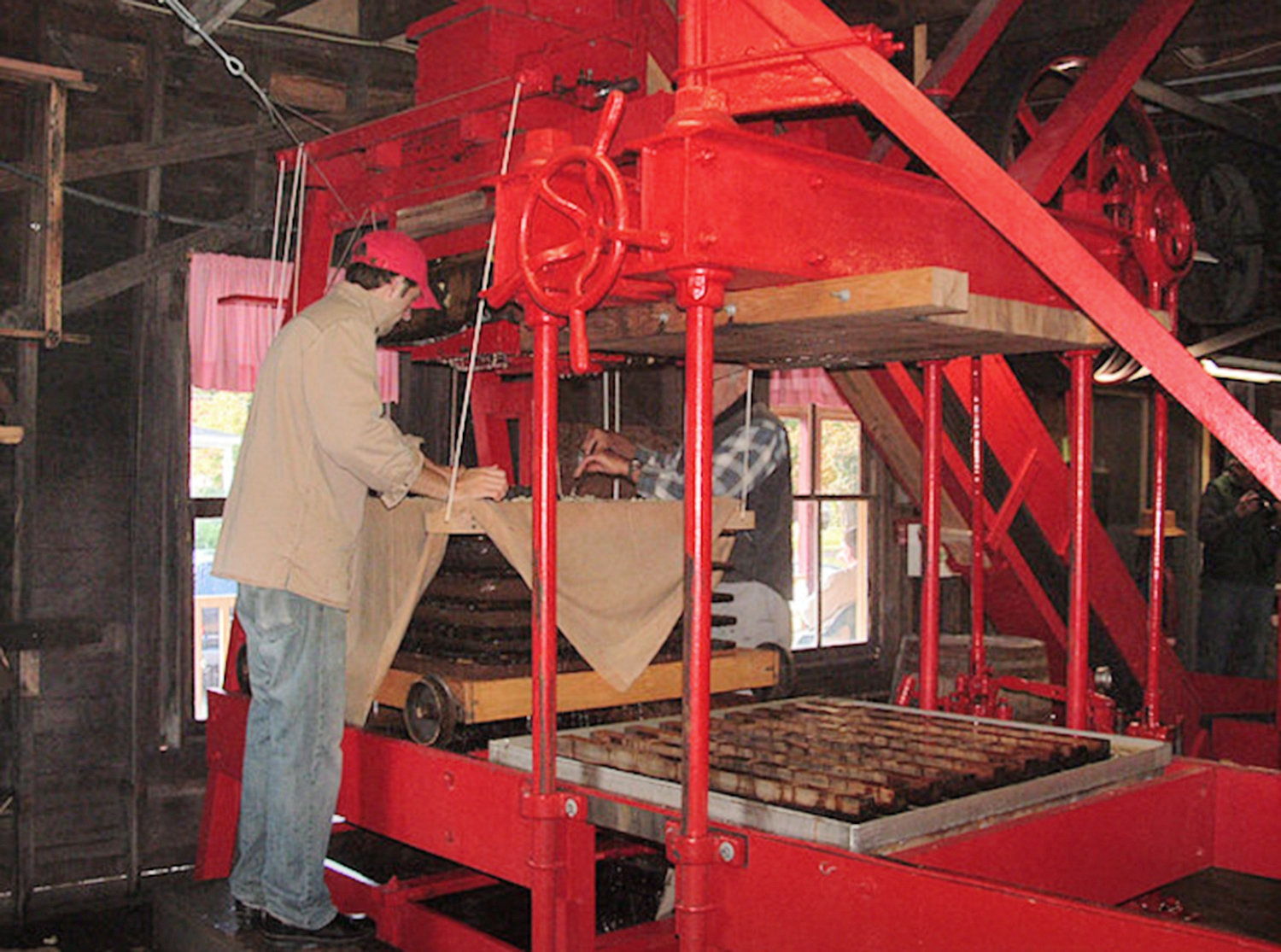 "PRESSING BUSINESS — Ben and John Fehlner build a ""cheese"" stack that will eventually be hydraulically squeezed to produce sweet apple cider in this apple pressing machine dating back to the late 1920s."