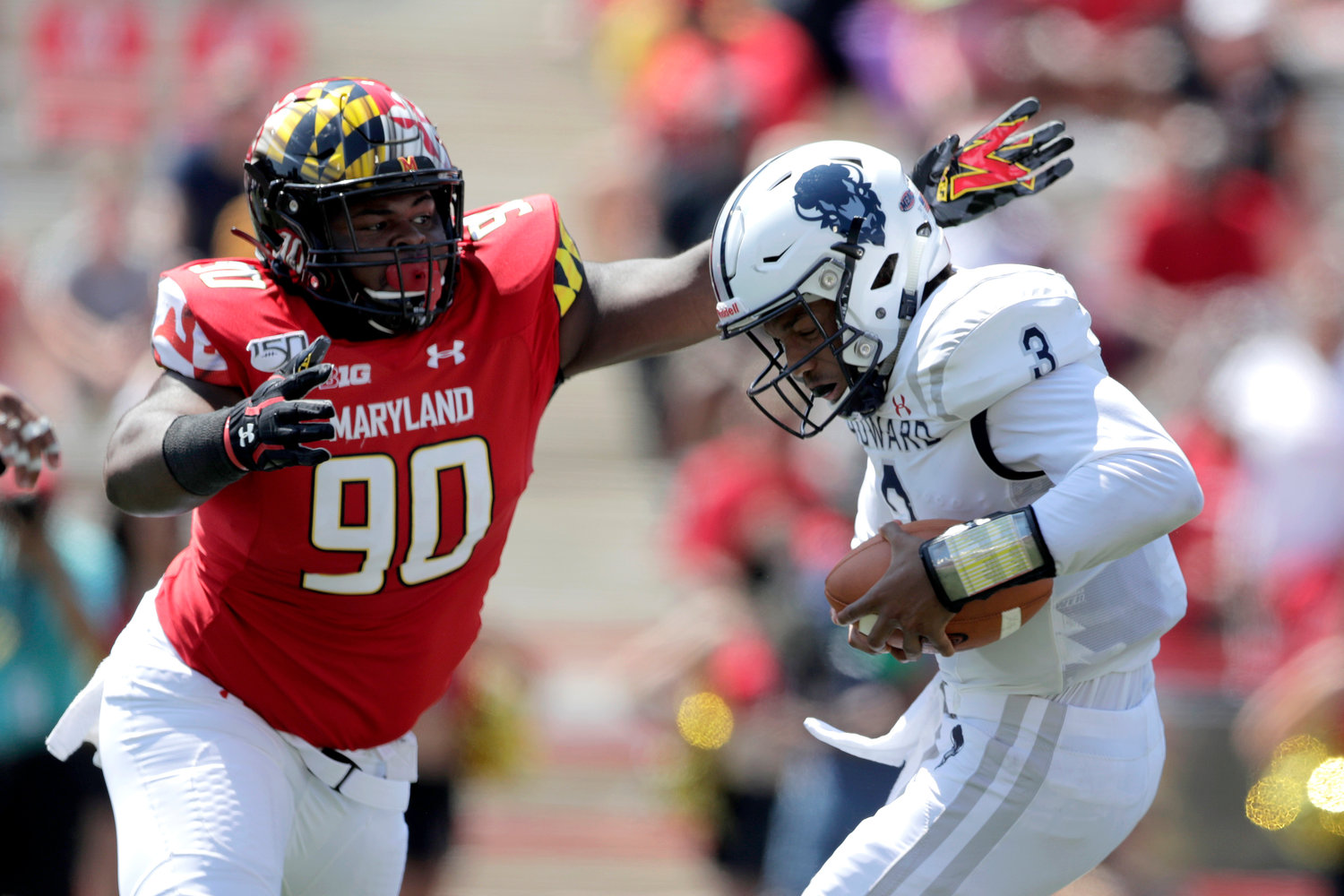SACK ATTACK — Maryland defensive lineman B'Ahmad Miller, left, moves in to sack Howard quarterback Caylin Newton during the first half of a game on Saturday in College Park, Md. The Terrapins won, 79-0.