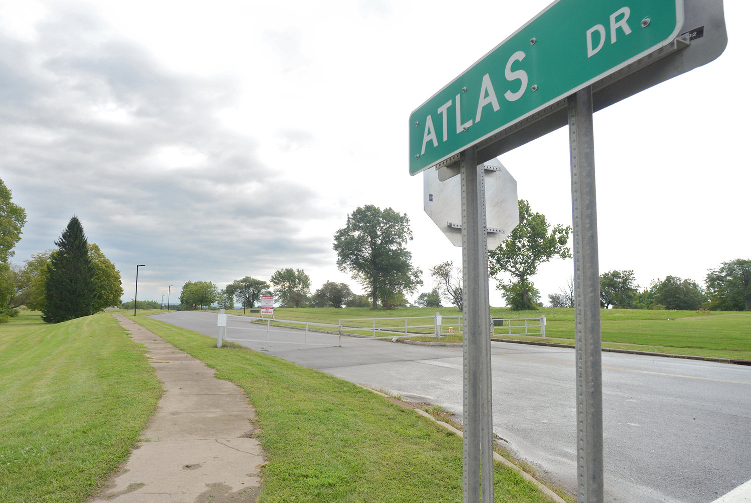 AT THE BEGINNING — A street sign marks the Atlas Drive intersection with Route 825 on the Griffiss Business and Technology Park. In the distance is a locked gate and construction site sign, heralding the proposed constructive of a massive new distribution center.