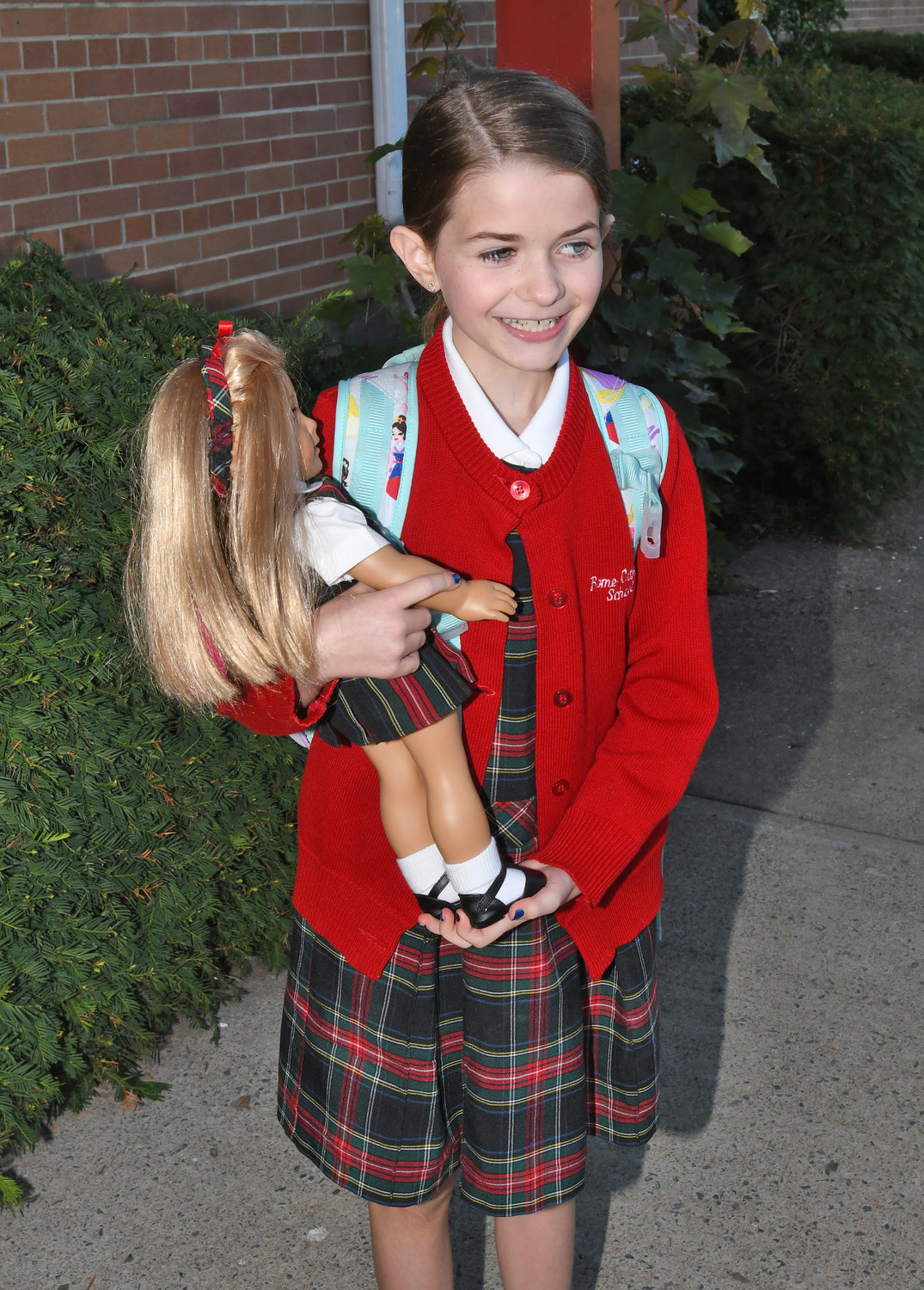 Isabelle Broughton 4th grader dressed in the school uniform with her doll that is also dressed up in the school uniform