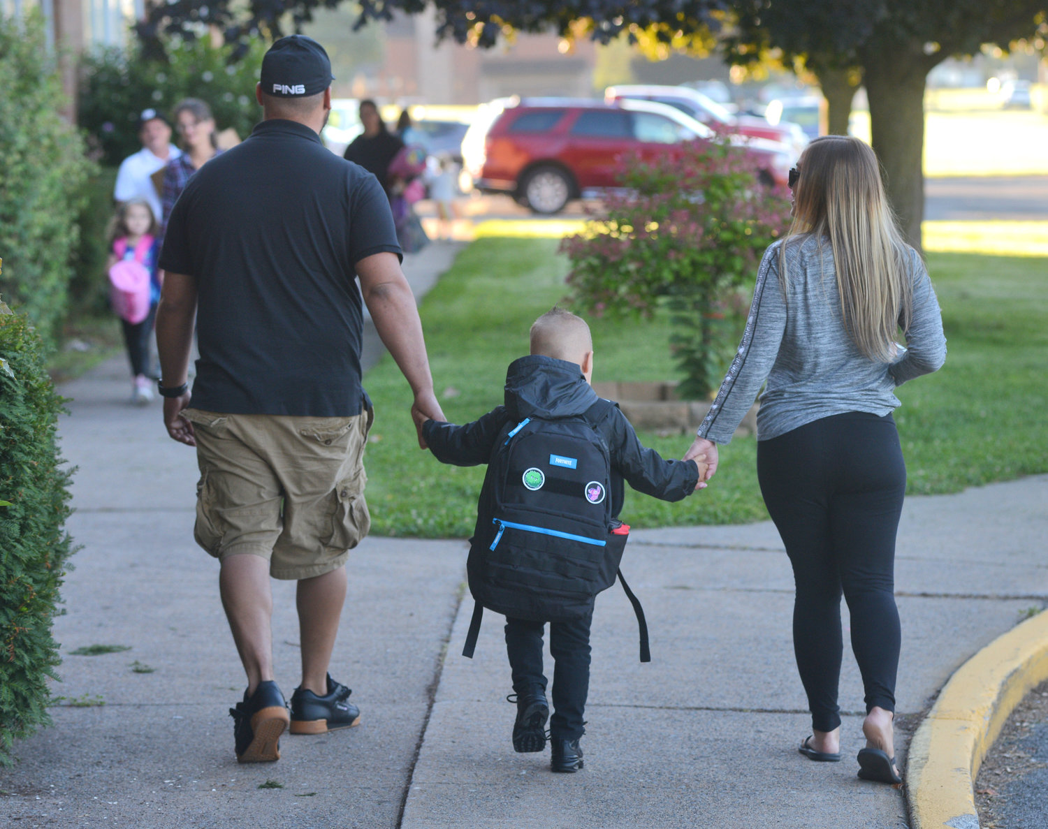 Max Eisinger and his wife Eisinger walk hand and hand with their son Mason, 4, who is going to his first day of pre-school at Rome Catholic.