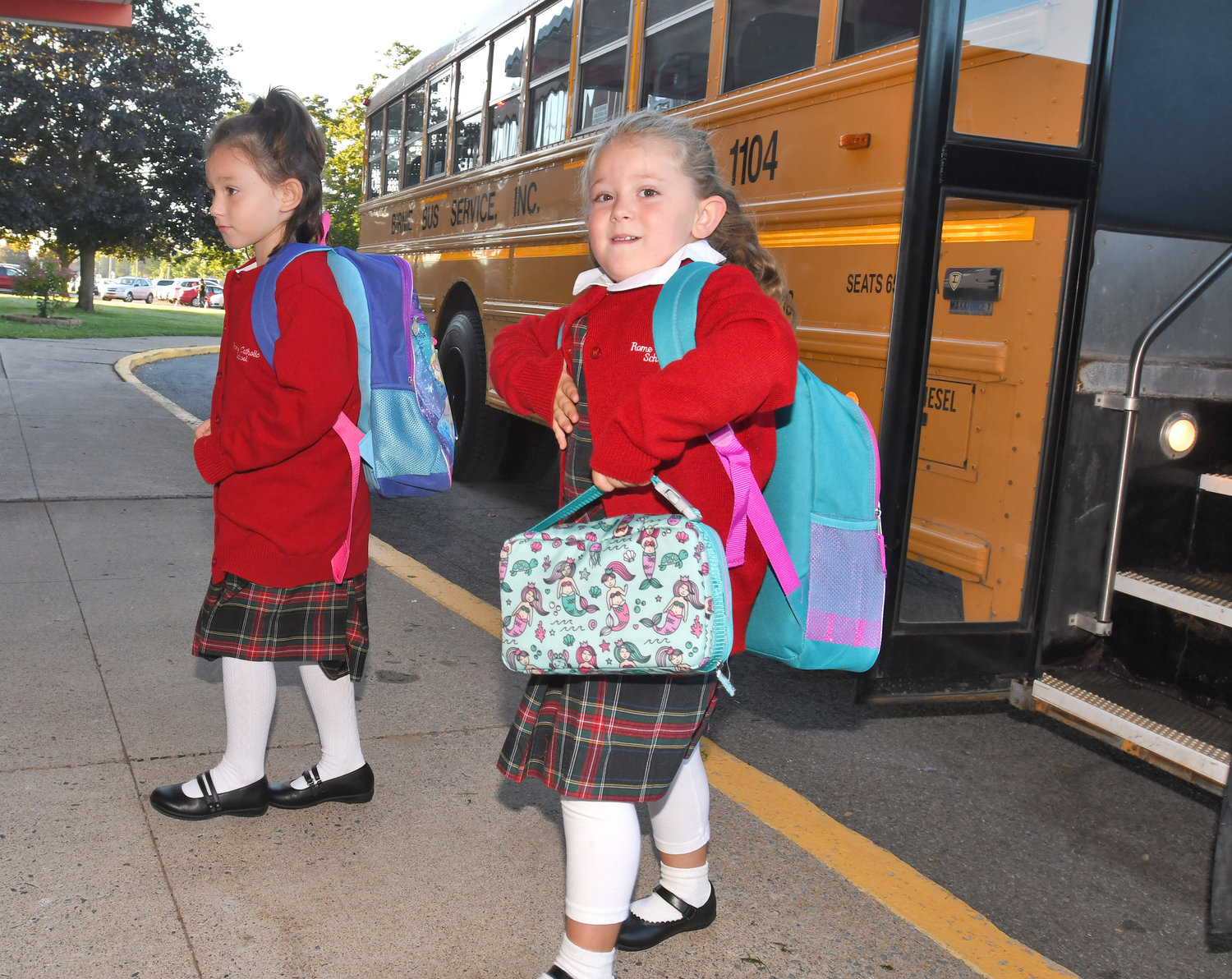 Rome Catholic students Milena Kittleman and Alessandra Schneider depart their bus Thursday morning on the first day of school. They are both kindergarteners.