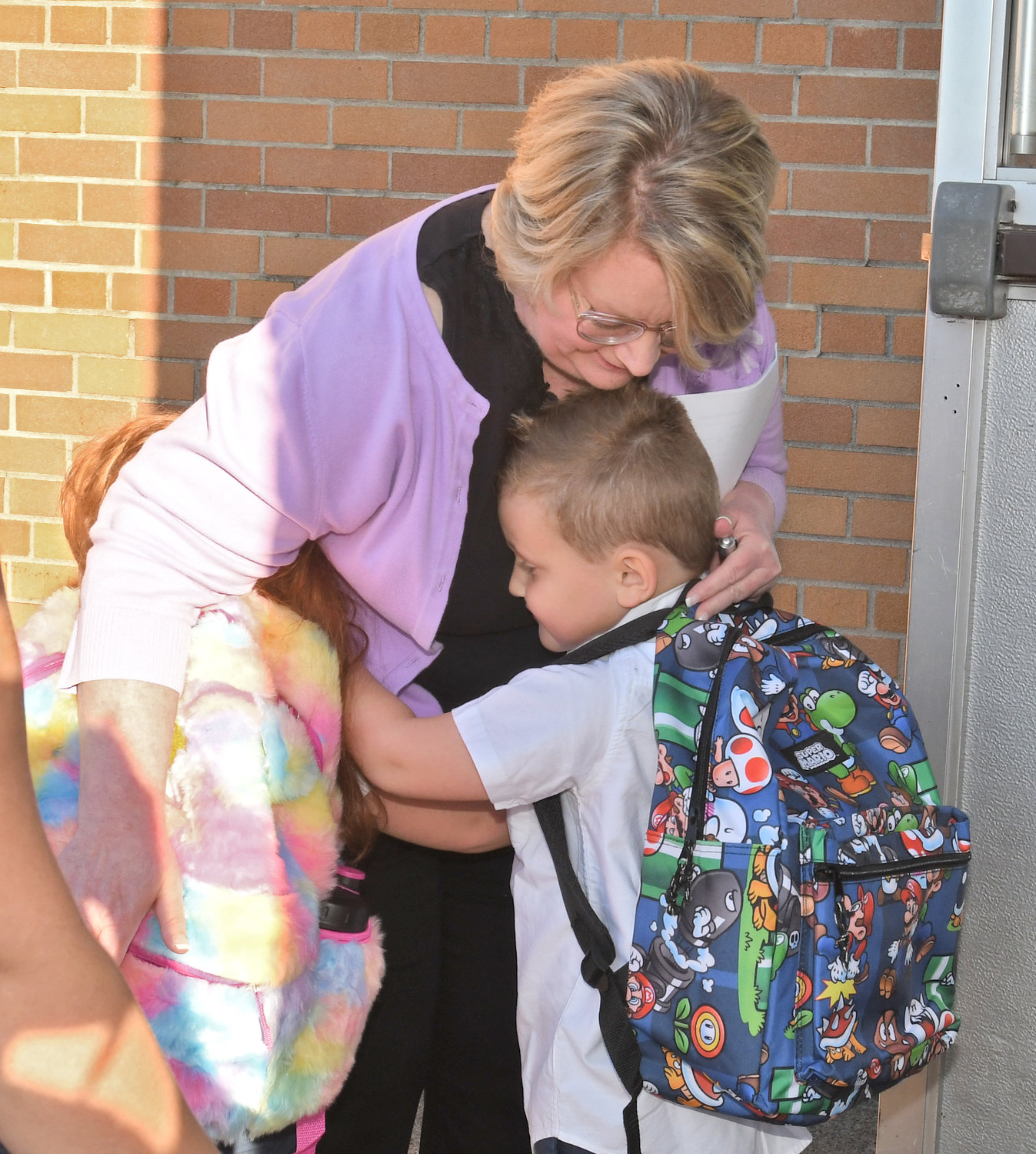 Adelyn and Jaxson Voorhees hug Rome Catholic principal Nancy Wilson on the first day of school