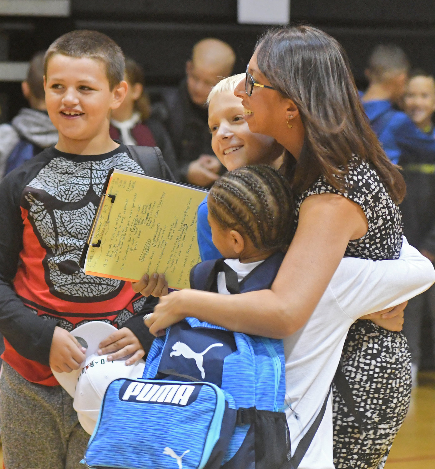 third grade teacher Mercedes Mills gets hugged by former students before the start of the new school year at Staley.
