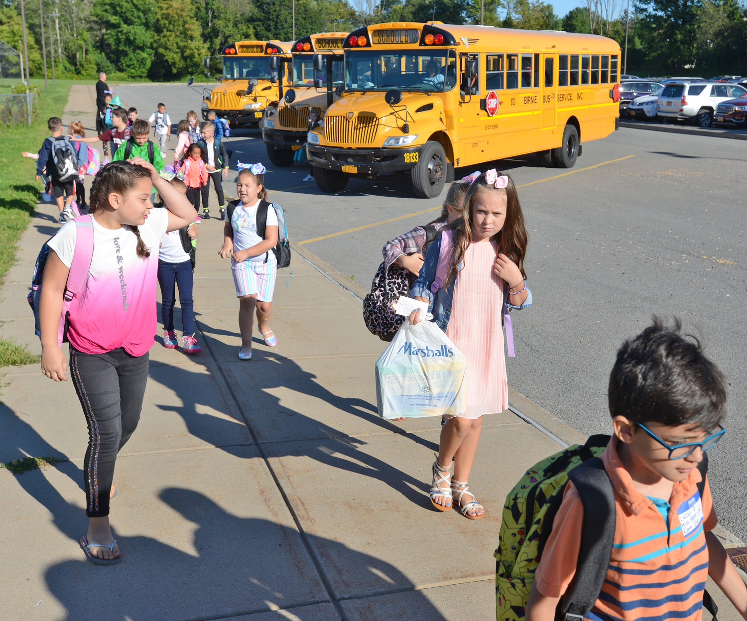 Children depart school buses at Staley Elementary School on their first day of school.