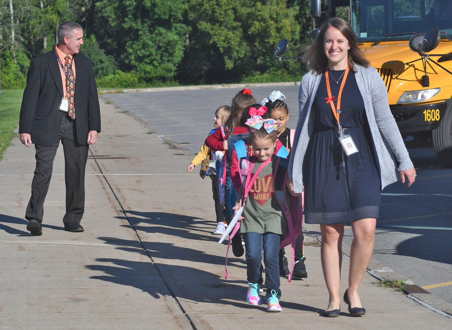 THIS WAY TO STALEY— Staley Elementary School teacher Mackenzie Welter leads her children to the school this morning for the first day of classes after they departed buses. At left is new Staley Principal Michael Davis, speaking to one of her students.