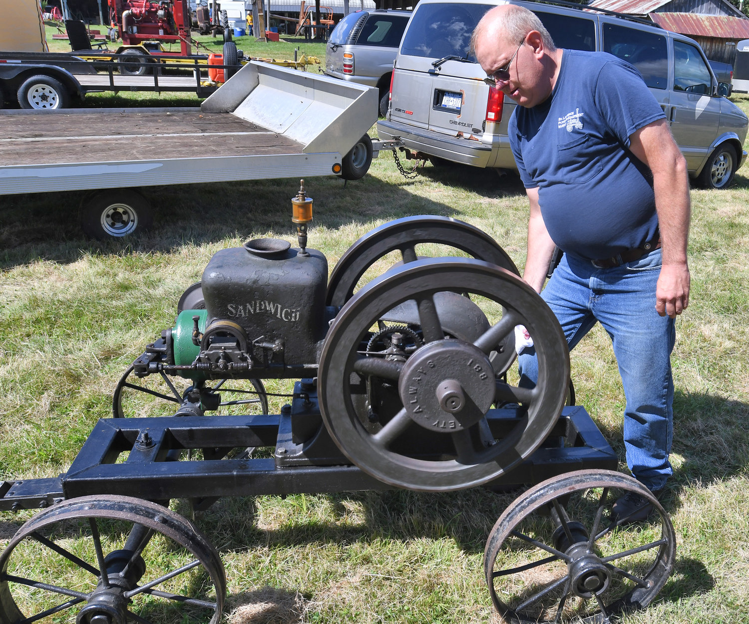 HIT AND MISS ENGINE — John Smith of Gouverneur puts stress on the flywheel of his 1917 Sandwich hit and miss engine to make it work harder and with more hits on Friday during the 44th annual Old Time Gas Engines, Tractors and Truck Show at the Flywheels and Pulleys Club in Constableville. The event is a fundraiser to support the nonprofit club.
