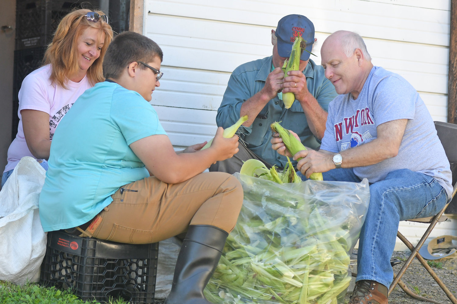 Corn is shucked for the  annual fish fry and at the Flywheel & Pully's Old Time Gas & Steam Engines/Flea Market Friday night in Constableville. Husking the corn left to right are: Mary Miller and her son Wareen Russell, Hobart Kraeger and Bud Shepherd.