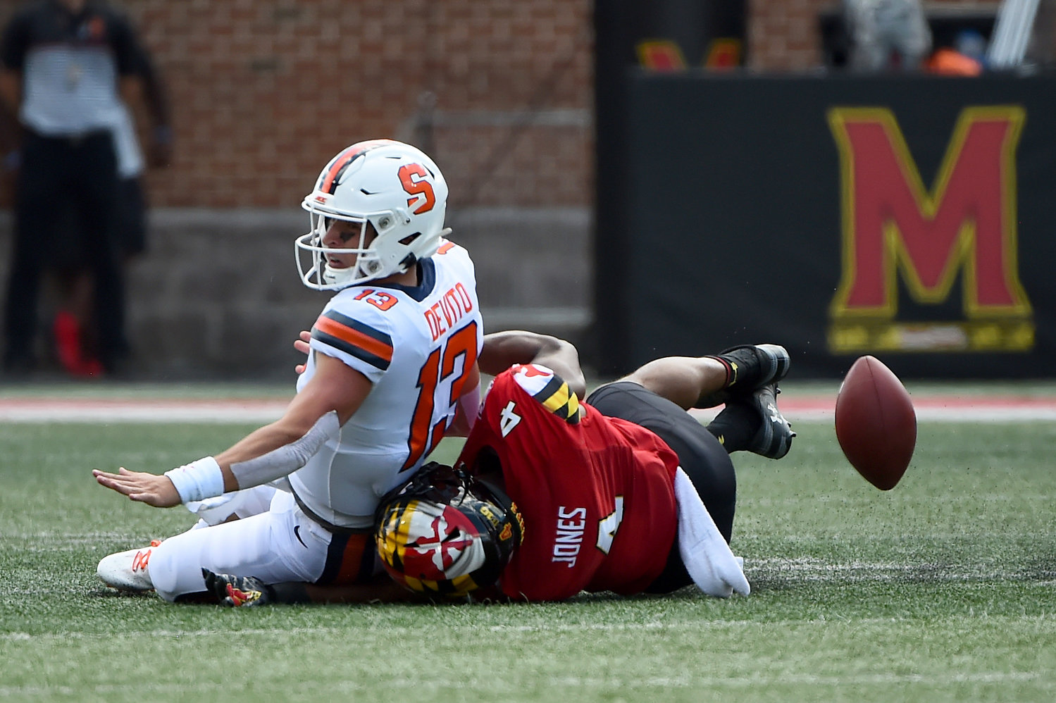 LOOSE BALL — Terrapins linebacker Keandre Jones (4) forces Orange quarterback Tommy DeVito (13) to fumble during the first half of a college football game on Saturday in College Park, Md. The Orange were routed 63-20.