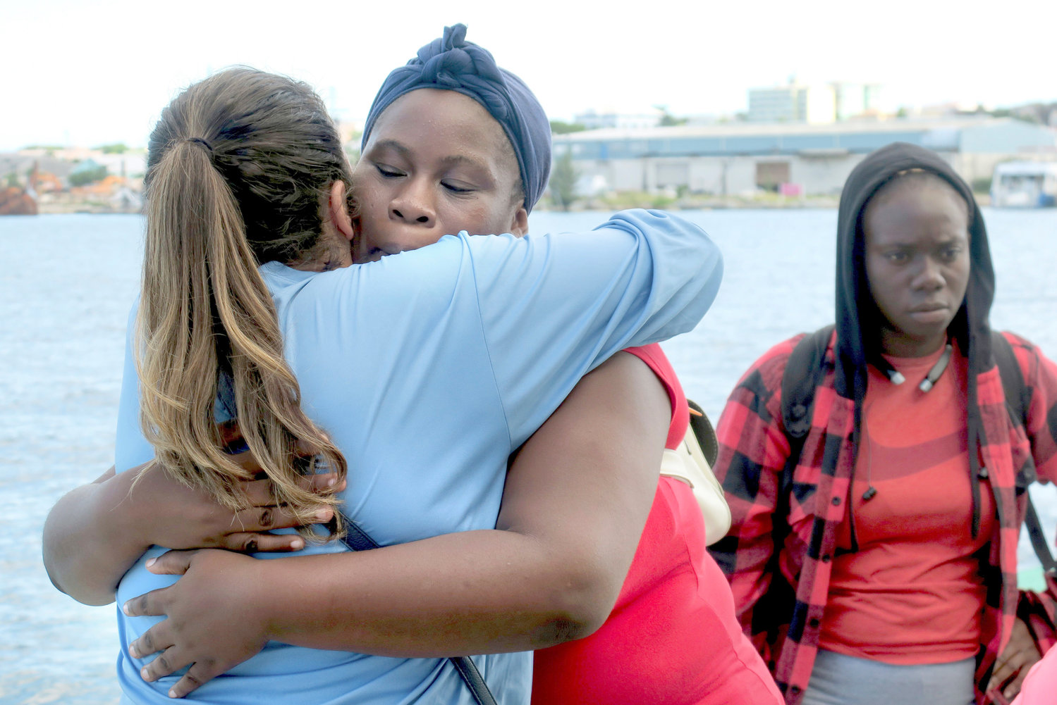 HUG GOODBYE — Akela Moxey, who was evacuated from Freeport, Bahamas, aboard Royal Caribbean's Mariner of the Seas cruise ship, hugs a Royal Caribbean employee, left, goodbye after arriving in Nassau, Bahamas, on Saturday. Freeport sustained devastating damage because of Hurricane Dorian.