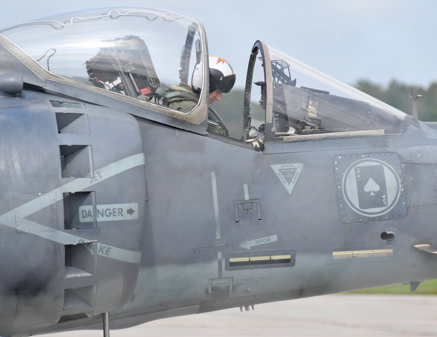 AWAITING FLIGHT — A pilot rests in the cockpit of his Harrier jet near the runway at Griffiss International Airport on Tuesday afternoon.  The aircraft — one of four Harriers from Cherry Point, N.C. — is roosting at Griffiss this week for a series of training exercises.