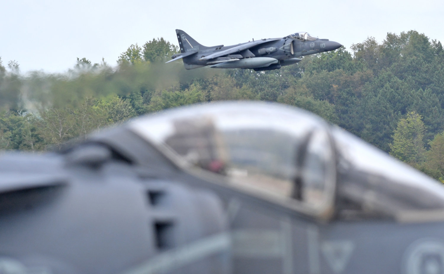 One of the two Harriers at Griffiss takes off with the cowl and cockpit of the other Harrier in the foreground.