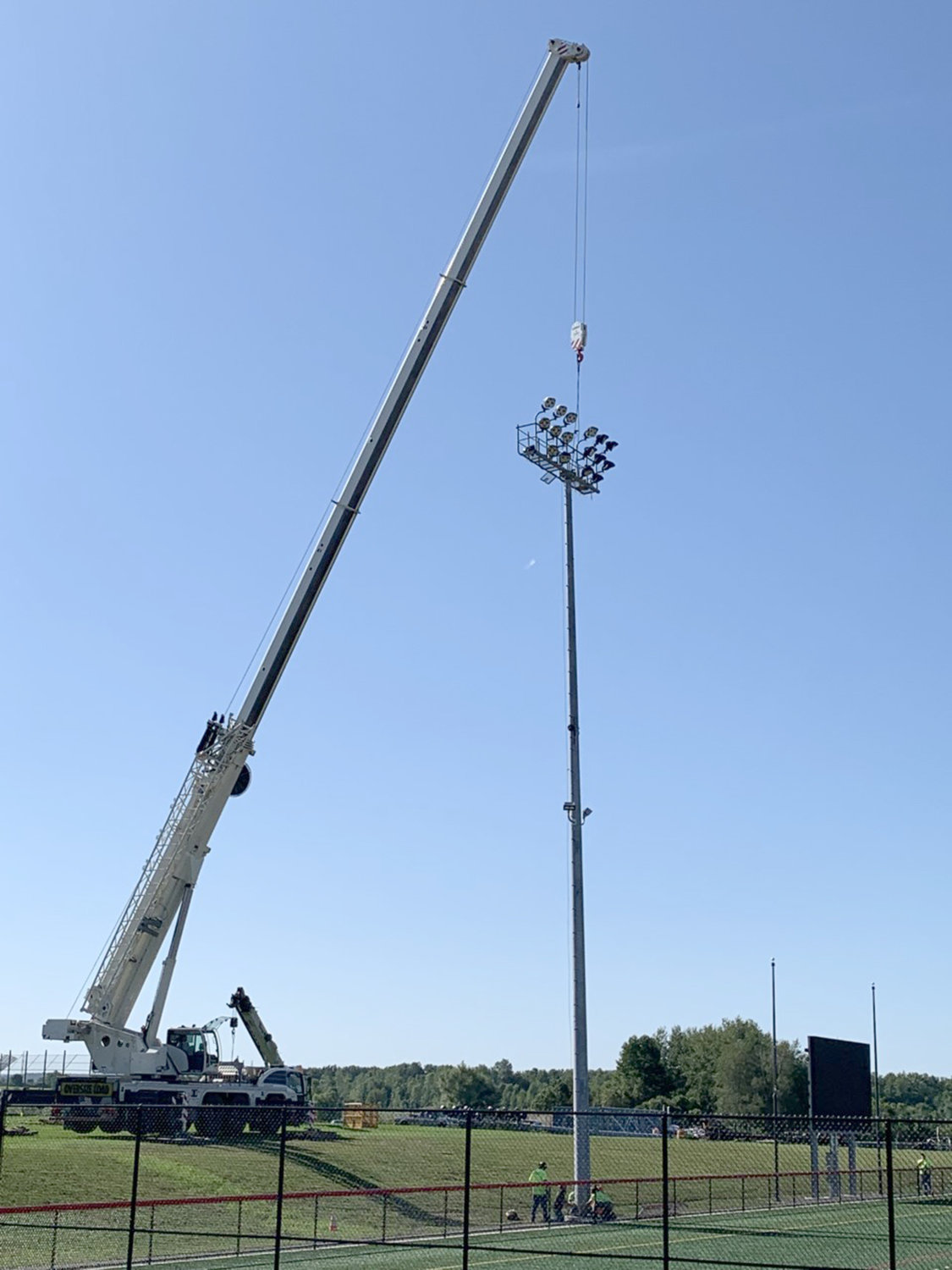 BIG REACH — A crane assists in the recent reinstallation of a light pole at the Vernon-Verona-Sherrill school district's Sheveron Stadium. Four poles containing sets of lights were brought down last spring due to structural concerns, but are back in operation after being reinstalled and undergoing final testing.