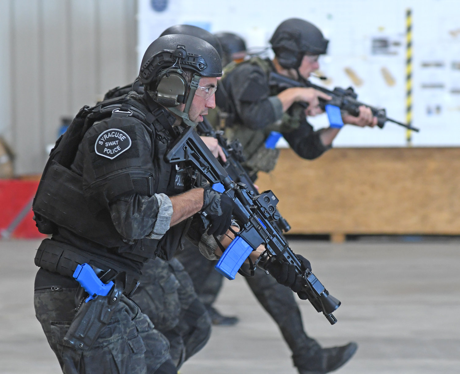 MOVE AND SHOOT — Members of the Utica and Syracuse SWAT teams practice running with their guns raised during one of several training sessions in Whitestown on Thursday.
