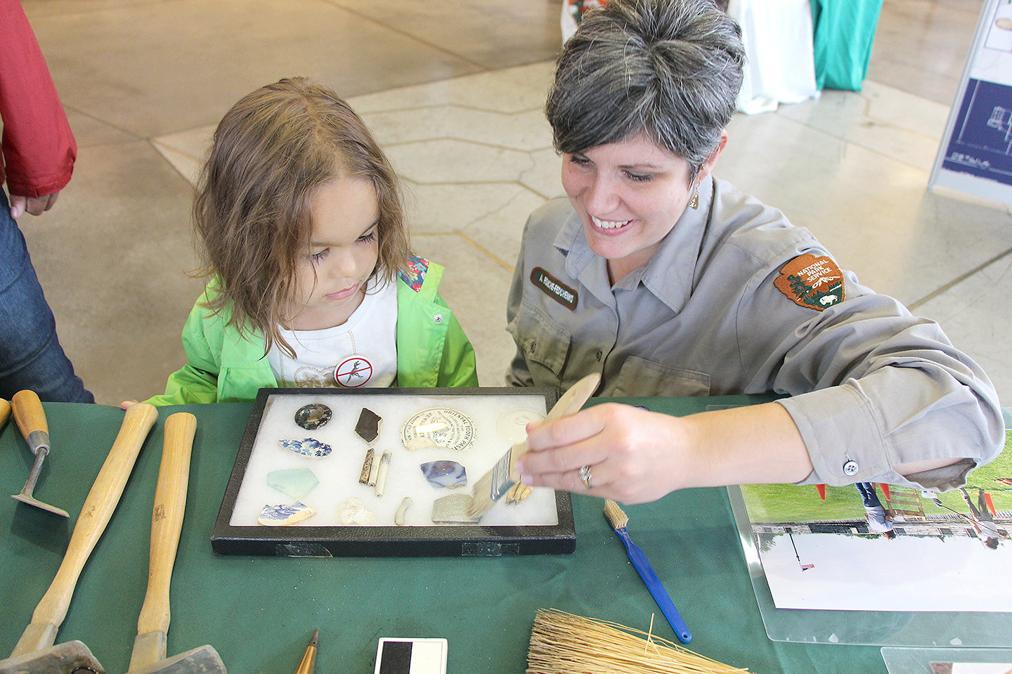 THE OLD BRUSH OFF — A park ranger shows a youngster how archaeologists uncover and explore artifacts.  Fort Stanwix National Monument will help visitors young and old learn more about the region's past during its annual International Archeology Day Celebration on Saturday, Sept. 28, from 10 a.m. to 4 p.m.