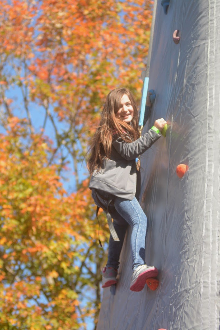 GOING UP — Mckenzye White 8, daughter of Kaitlin White, scales the inflatable rock wall during Locktoberfest on Saturday.