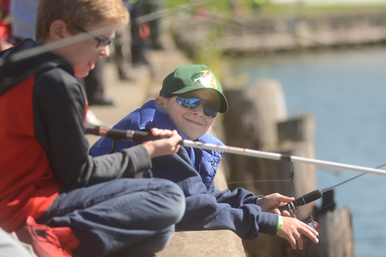 FISHING FUN — Carlo Anthony, 10, son of Ed D'lessandro gives a smile as a fishes from the dock at Bellamy Harbor during the Youth Fishing Derby presented by the Rome Police Department Benevolent Association on Saturday.