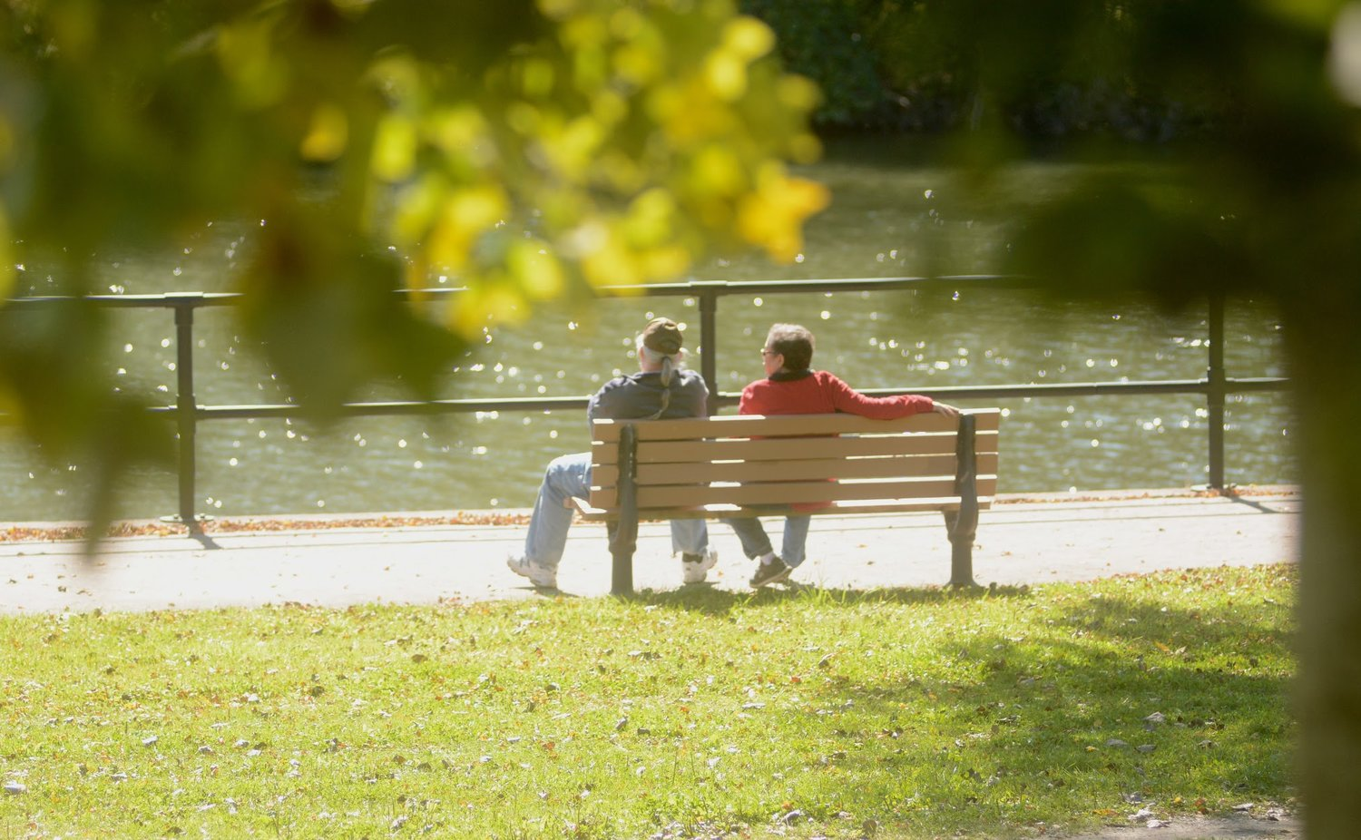 A couple sits by on a bench by the water on a perfect fall day.