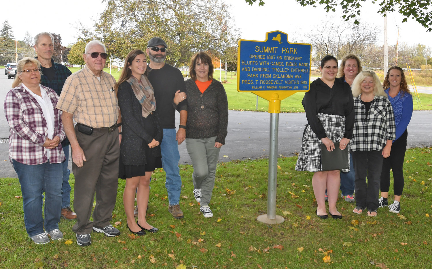 CELEBRATING THEIR HISTORY — Members of the board of directors for the Battle of Oriskany Historical Society gather around the new historical signage at Summit Park in the village. From left: Amy Kasprzyk; John Kasprzyk, village of Oriskany trustee; Charles Smith, historical society treasurer; Kelley Bogner; Jim Miller; Deb Miller; Alexis Werchowski Albright, Oriskany Museum curator; Jennifer Werchowski; Pam Tarasiewicz; and Stacy Lindfield. The signage was made possible, in part, by a gift of the William G. Pomeroy Foundation.