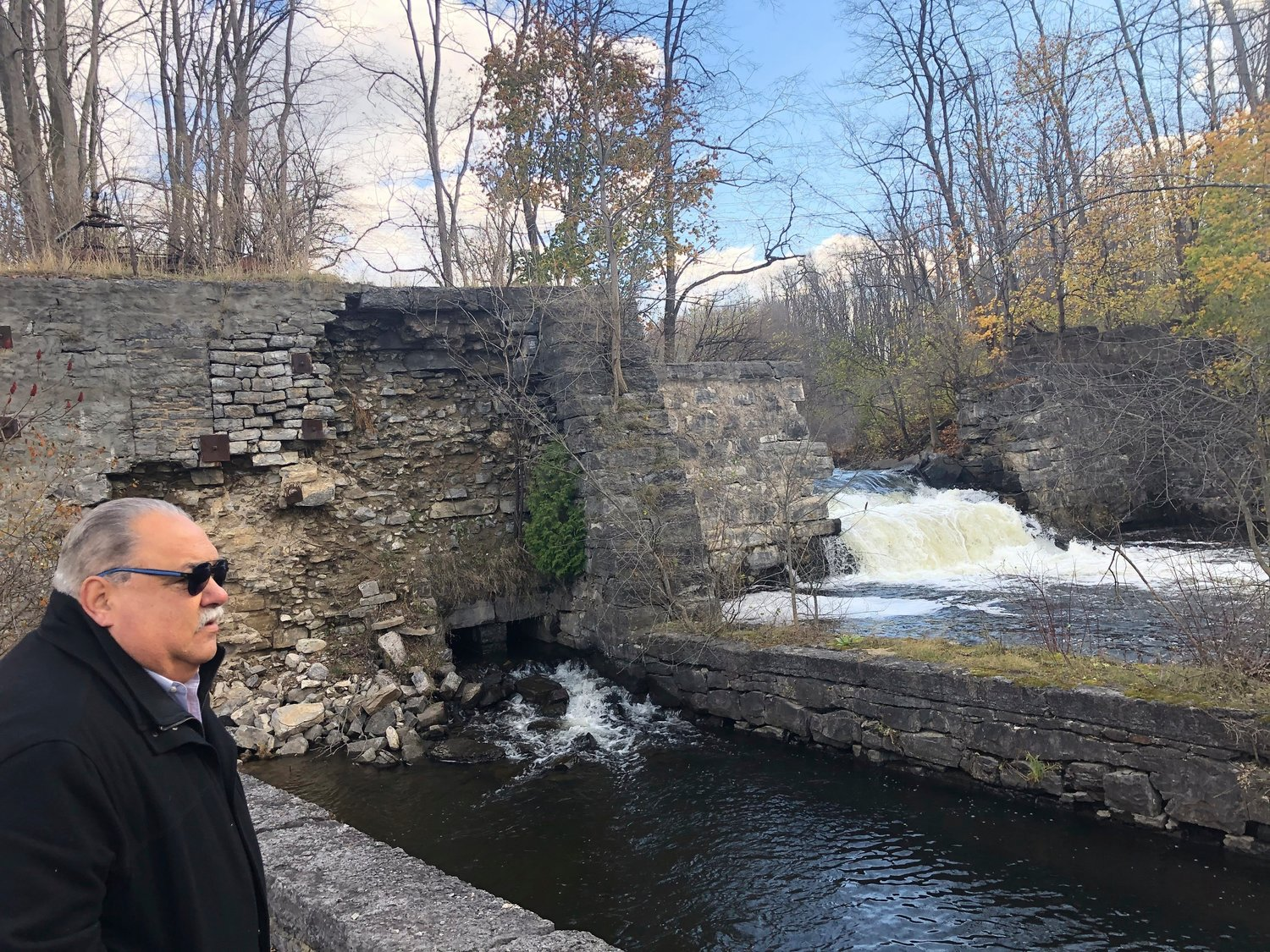 In this Wednesday, Nov. 6, 2019 photo, Amsterdam Town Supervisor Tom DiMezza stands beside the Harrower Pond Dam in Amsterdam, N.Y., one of 48 high hazard dams in poor or unsatisfactory condition in New York state. State inspectors have noted numerous problems including cracks, seepage, fallen stones and trees growing on dam structures. The center of the dam has been breached by the state Department of Environmental Conservation to reduce the volume of impounded water. (AP Photo/Mary Esch)