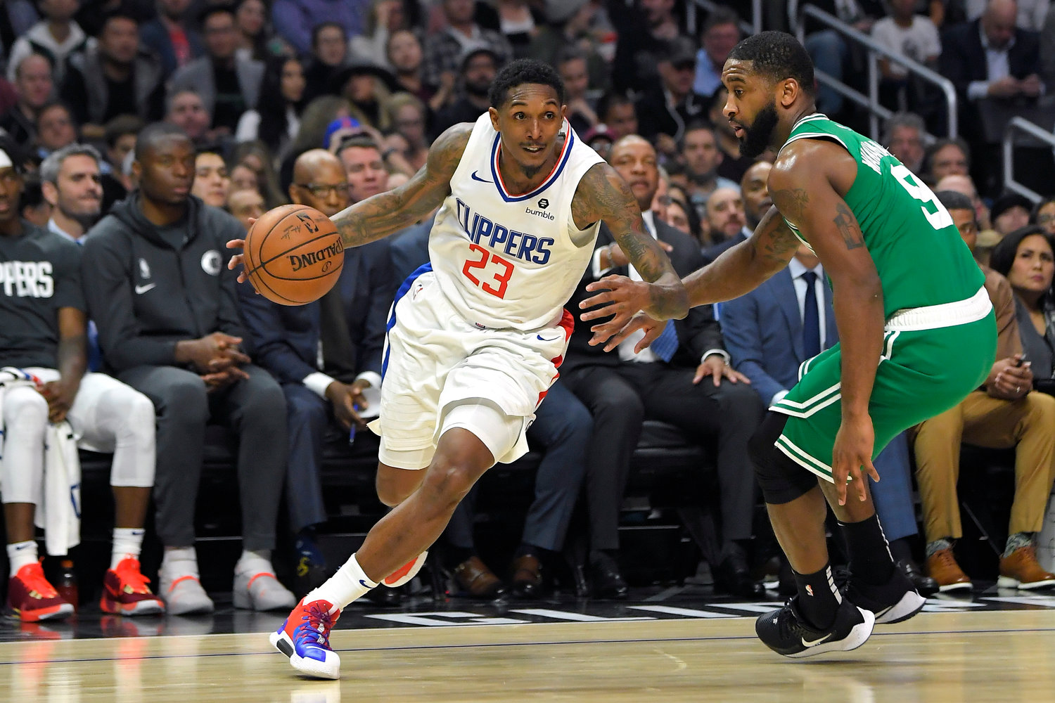 DRIVING BY — Clippers guard Lou Williams, left, drives past Celtics guard Brad Wanamaker during the second half of an NBA game on Wednesday night in Los Angeles. Williams scored 27 points in the Clippers' 107-104 overtime win.