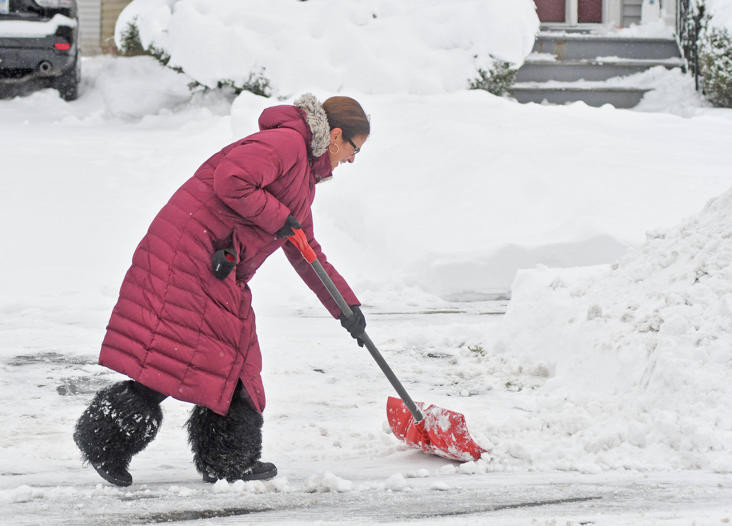 CLEANING UP — Francine Chilkotowsky, of 902 N. James St., cleans up her driveway after city plows made a pass down the roadway this morning. A winter storm dumped over a foot of snow on parts of the region from Sunday morning through this afternoon, scuttling a return to school for most area students and prompting state and local travel advisories. Occasional snow is expected to fall through tomorrow morning, and a winter storm watch, issued by the National Weather Service in Binghamton, is set to expire tonight at midnight.