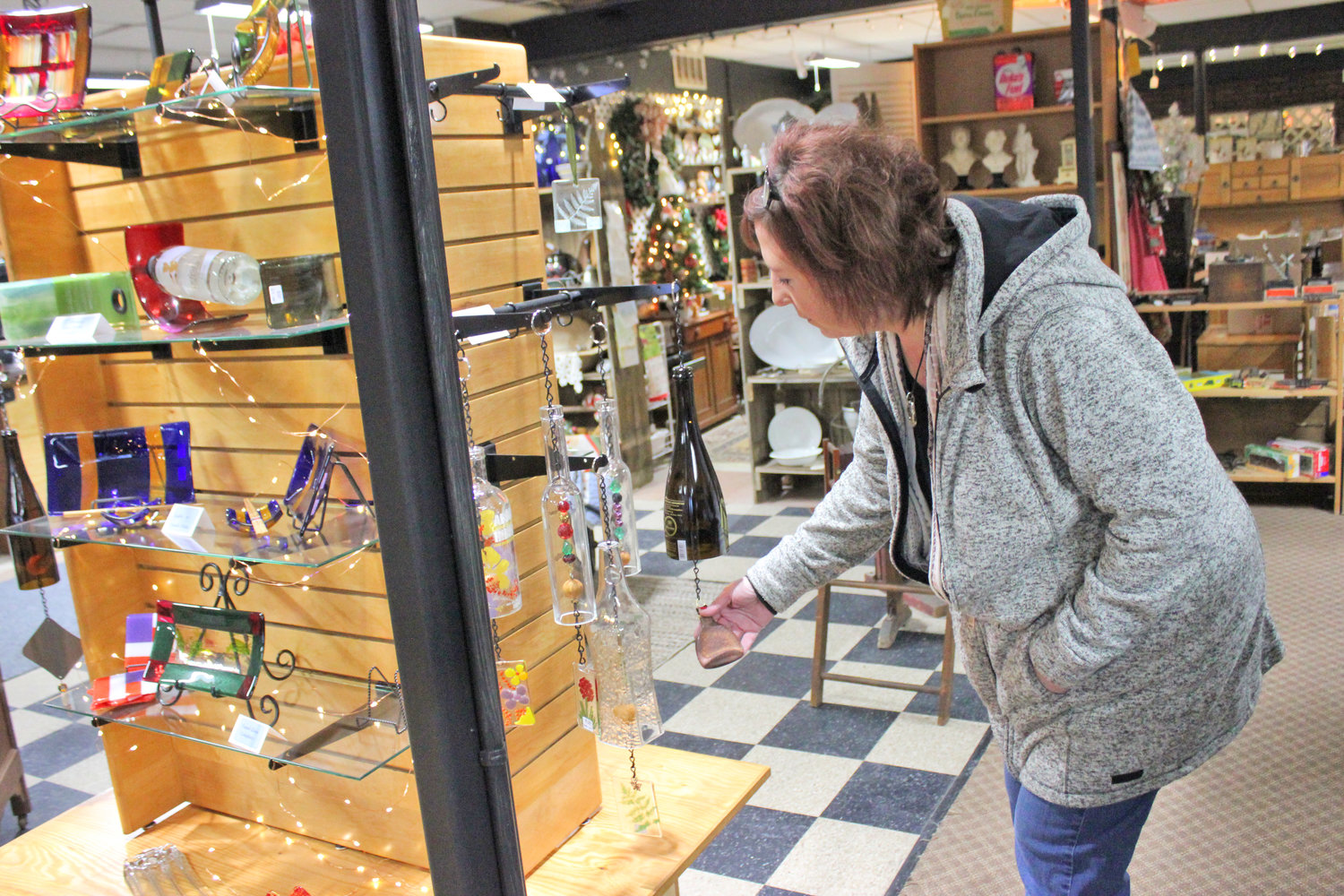 HANDMADE FINDS — Eclectic co-owner Valerie Thron-Pollack looks over handmade glassware made by Chittenango artist Cindy Helmer on sale at the Eclectic Mercantile.