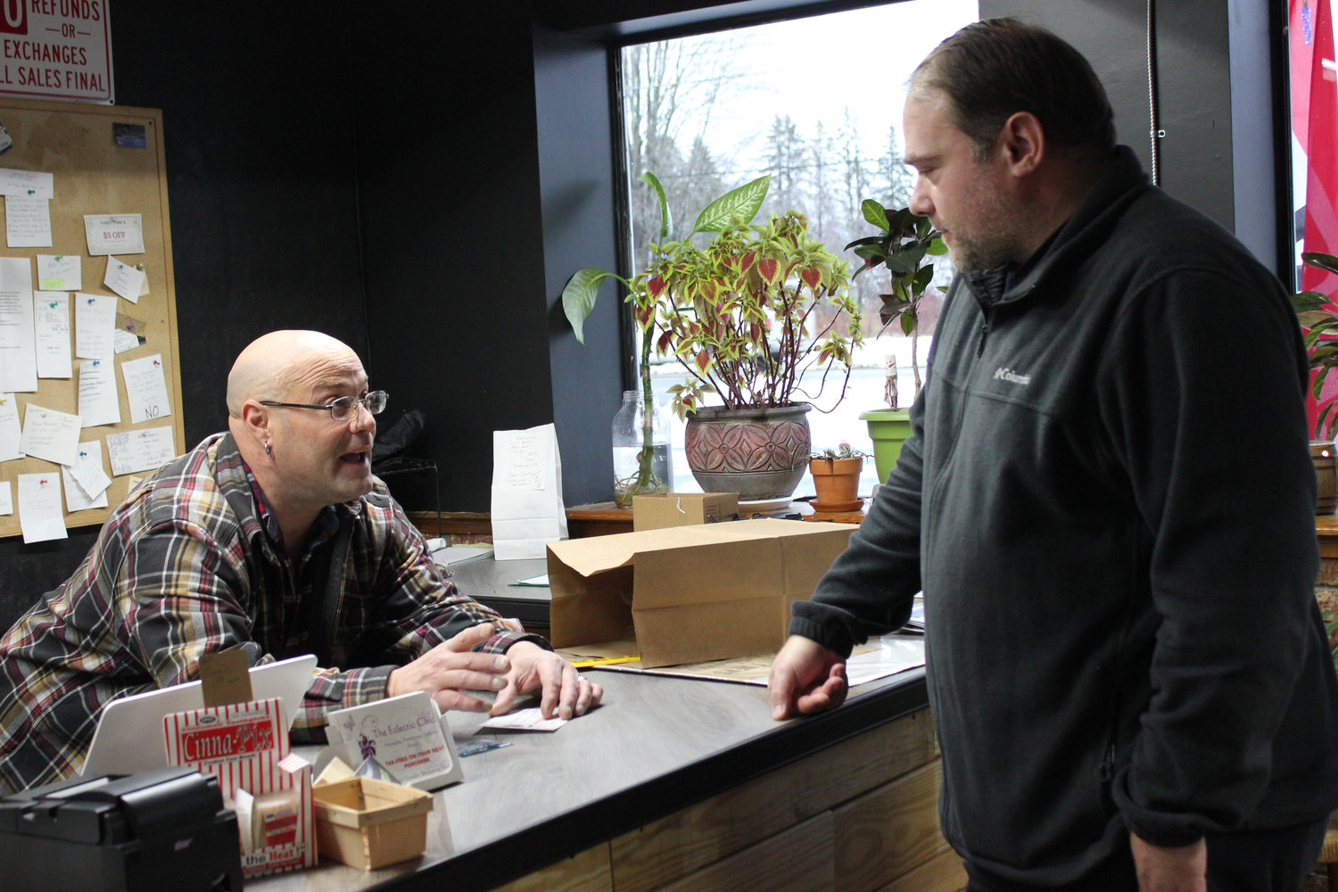 TALKING SHOP — Eclectic co-owner Darren Pollack, left, talks with local author Peter Leonard at the Eclectic Mercantile.