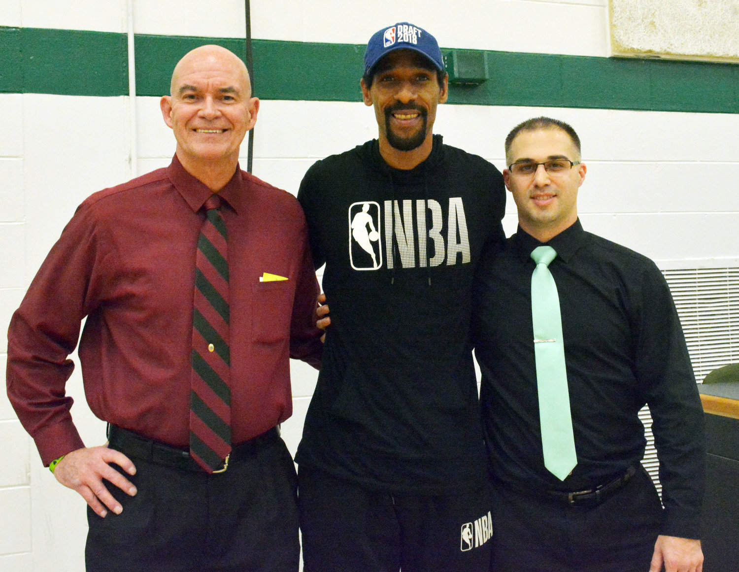 CAUGHT BETWEEN COACHES — Moten between Oriskany basketball coach Rick Cooke and Westmoreland basketball coach Nick Facciolo all take a minute before tip off to show their support for Lawrence Moten Night on Friday, Dec. 13 at Westmoreland High School.