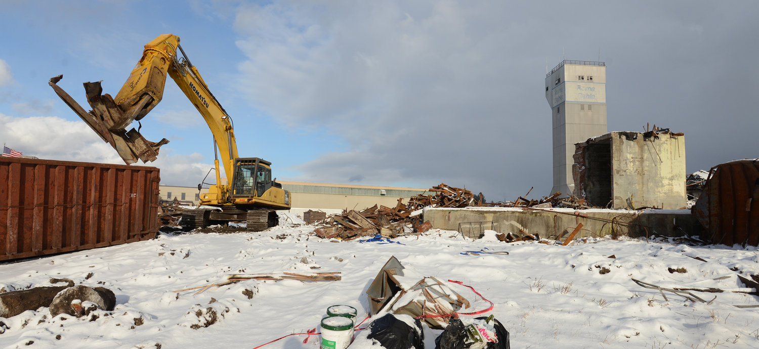 TEAR DOWN — An excavator picks up metal at the former Rome Cable site on Wednesday.