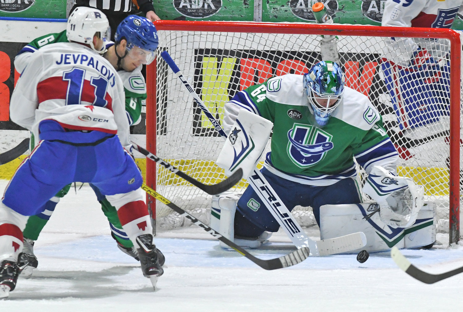 Laval #11 and Comets #6 in front of Comets with a shot on the Comets goalie.
