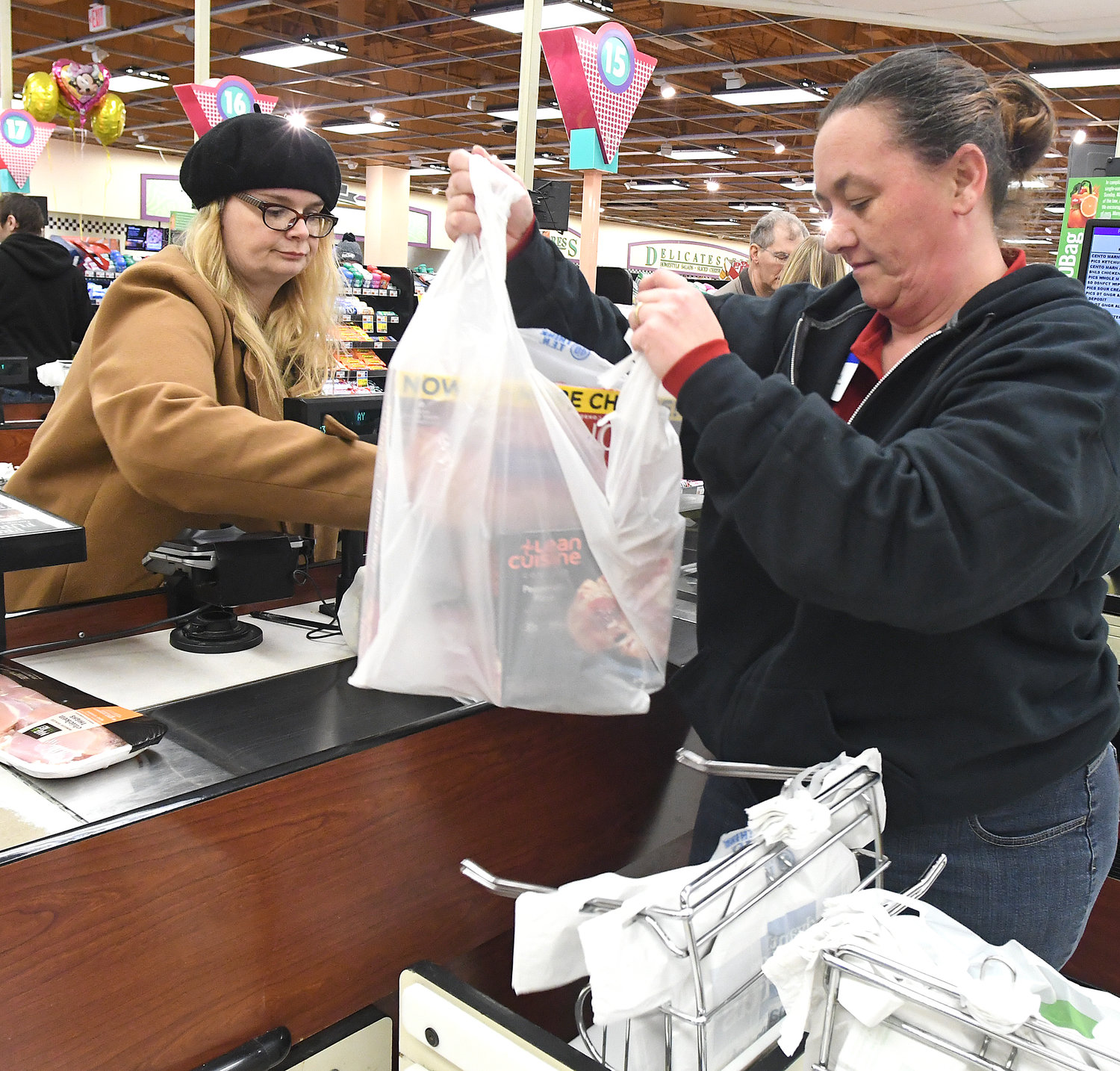 "LAST BAGS — Price Chopper employee Charlene Whaley uses store plastic bags for customer Holland Saenger. When asked what she would be doing for bags Saenger laughed and said, ""Stop shopping."" And then, ""I'll figure it out."" Whaley has been a Price Chopper employee for two weeks. She said a customer from Germany recently noted that back home, she normally carried her own container for grocery shopping."
