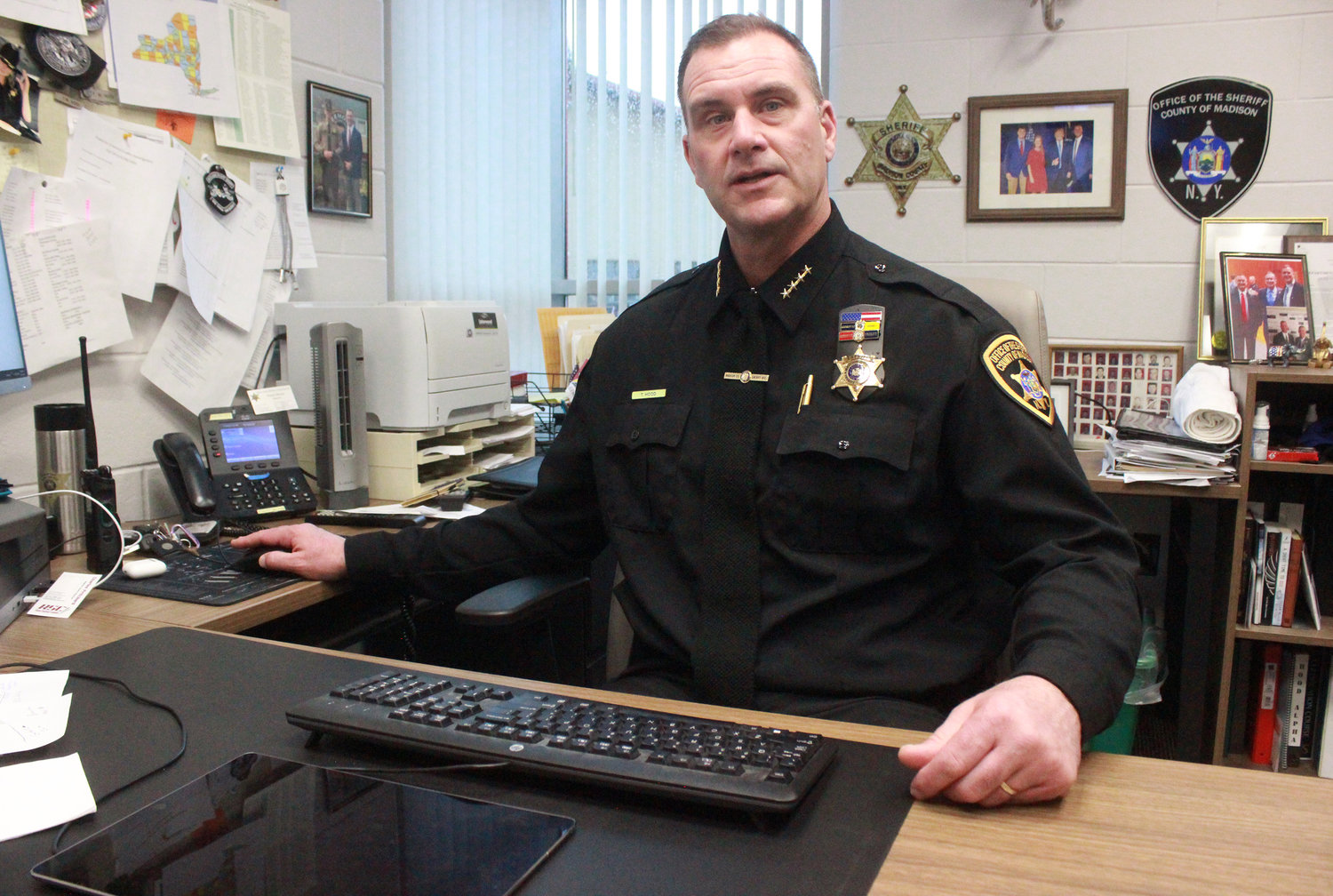 REACHING OUT — Madison County Sheriff Todd Hood sits in his office while discussing the importance — and availability — of Project Lifesaver and its ability to help locate at-risk people who have wandered.