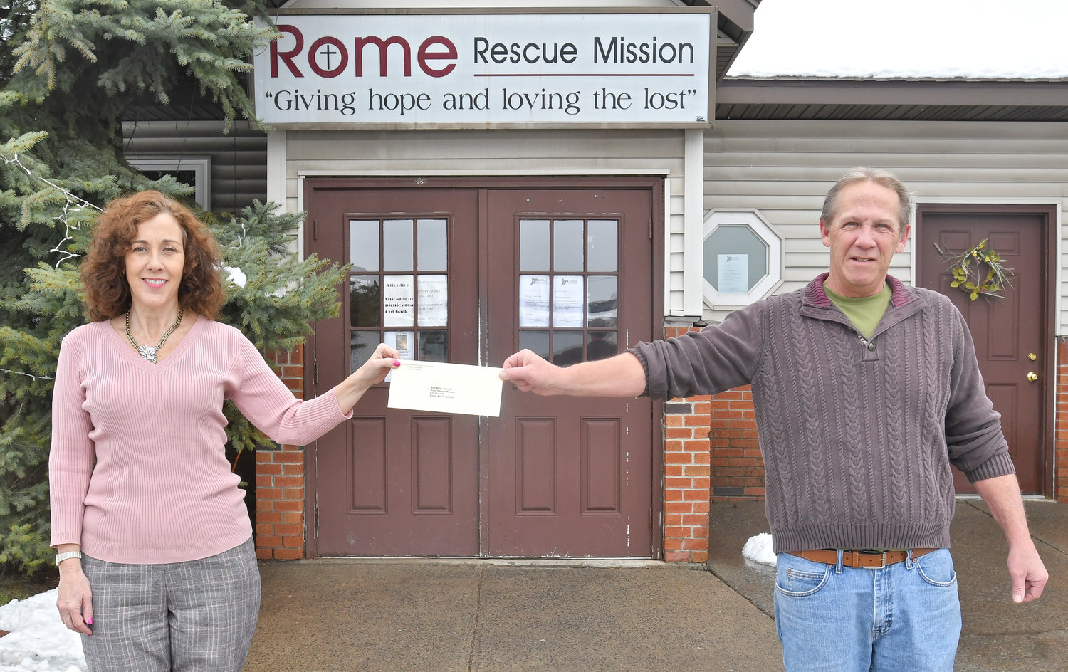 PASS IT ON — Dyann Nashton, of the Griffin Charitable Foundations, passes a check to Matt Miller, executive director of the Rome Rescue Mission on Tuesday afternoon. The foundations are calling on members of the community to help agencies, such as the Rome Rescue Mission, which are stretched to the limit trying to help the growing numbers of those in need in the community by also making monetary donations or helping serve others by volunteering.